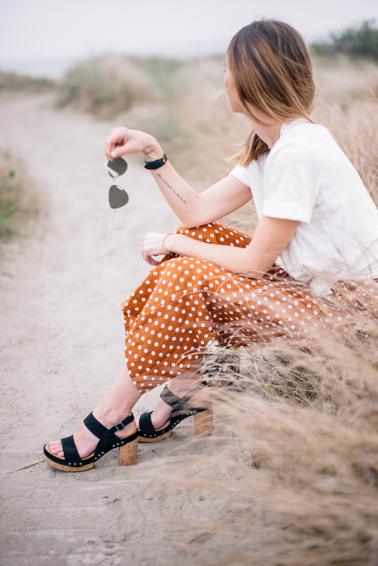 Jess Ann Kirby relaxes on the beach in statement wide leg pants from Faithfull