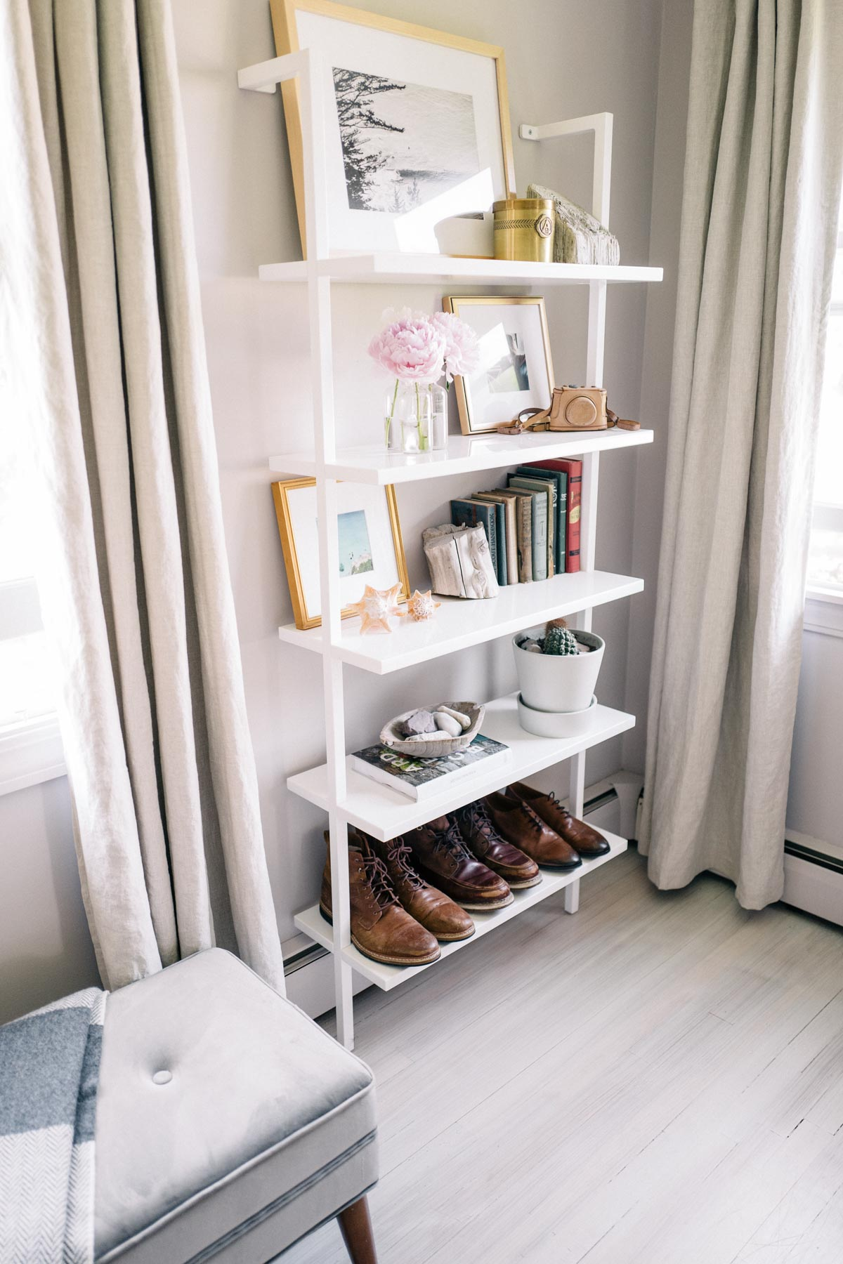 Jess Ann Kirby styled CB2 wall mount shelves with books, shoes and pieces of art