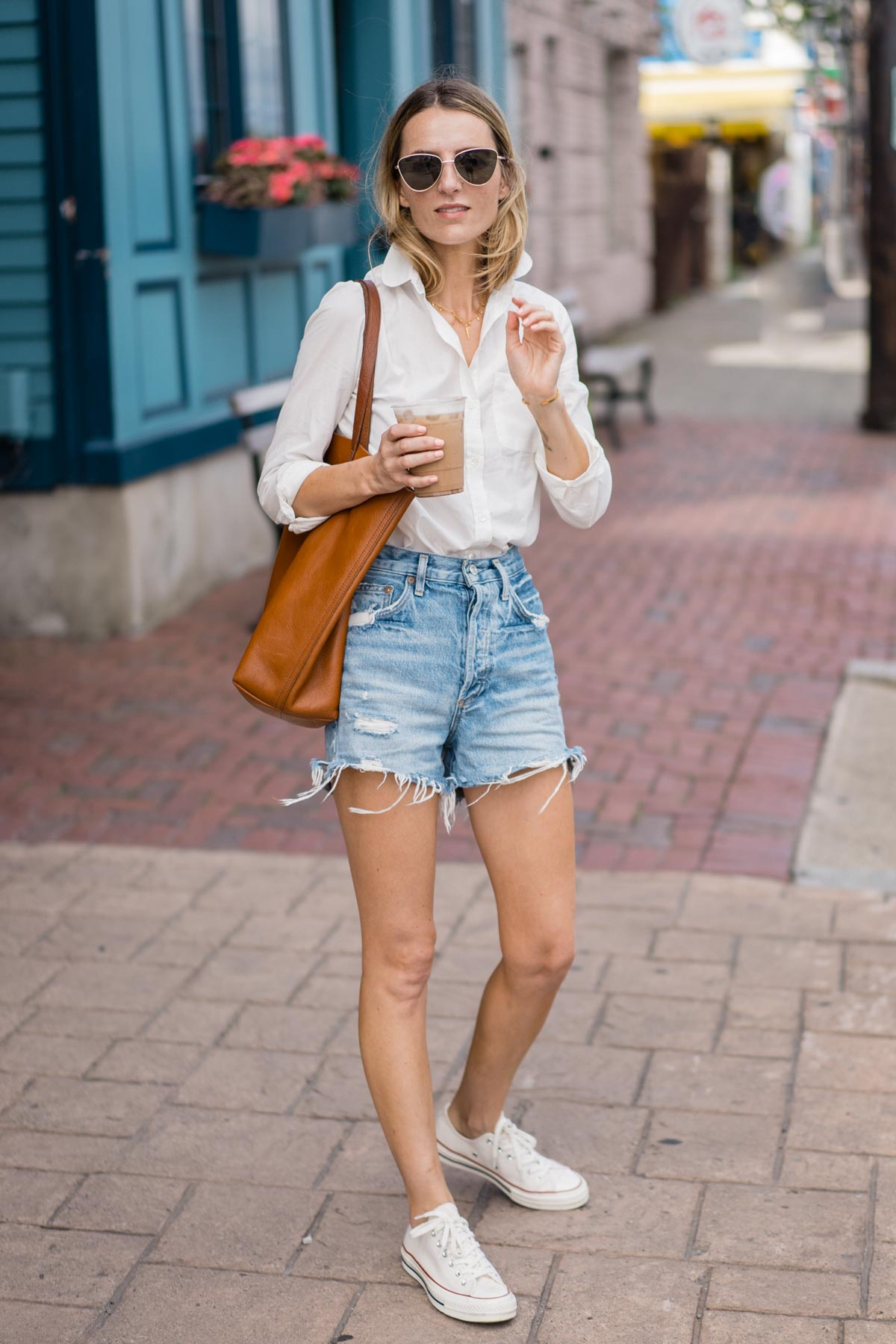 Jess Ann Kirby wears Agolde Dee Denim shorts with a classic white button down